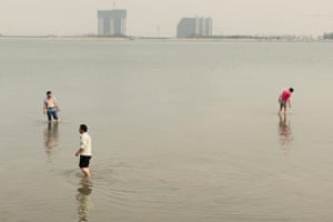 Locals fish for crabs in the Bohai Sea as construction sites stand idle in the background.