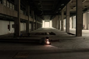 A lone worker inside Caofeidian city's mostly abandoned industrial park. He works for a company producing solar panels – a heavily subsidised industry in China that is plagued by over capacity.