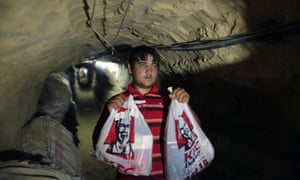 A smuggler carries bags of food from Kentucky Fried Chicken through an underground tunnel linking the Gaza Strip to Egypt in May 2013.