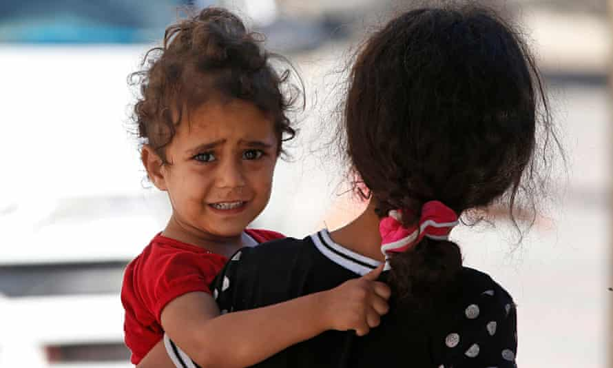 A girl cries as Palestinians flee their homes in Gaza City