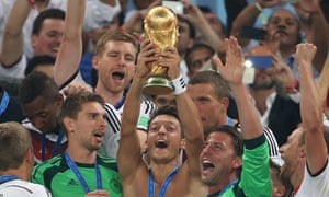 Mesut Ozil holds the World Cup trophy with his teammates during the trophy presentation after the match between Germany and Argentina.
