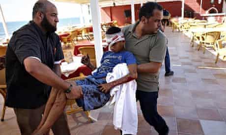 Palestinian al-Deira hotel employees carry a wounded boy - gaza port shelling