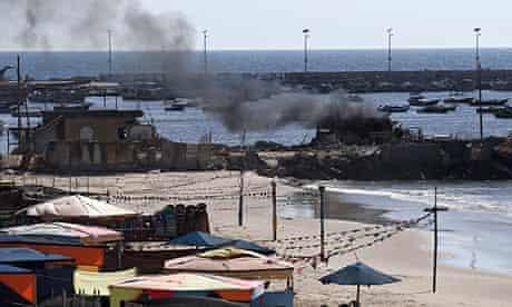 Smoke billows from a beach shack following an Israeli military strike - gaza port shelling