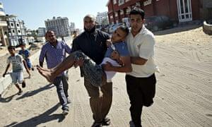 Employees of Gaza City's al-Deira hotel carry a wounded boy following a strike - gaza port shelling