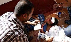 Employees of Gaza City's al-Deira hotel take care of a wounded boy -  gaza port shelling
