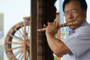 A Songdo resident plays the flute in the shade of a traditional Korean wooden shelter.