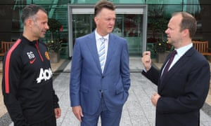 New Manchester United manager Louis van Gaal oses with assistant manager Ryan Giggs and executive vice-chairman Ed Woodward at the club's training complex.