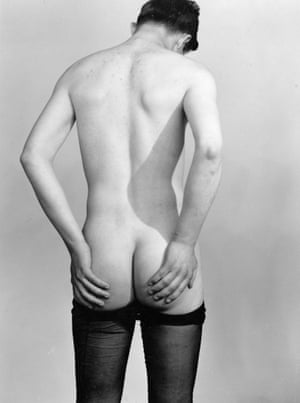 Back view of standing figure, nude except for stockings