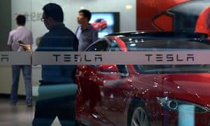 People visit a Tesla showroom in Beijing on July 9, 2014.
