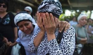 An Israeli woman mourns in Yehud, east of Tel Aviv, before the funeral of Dror Khenin.