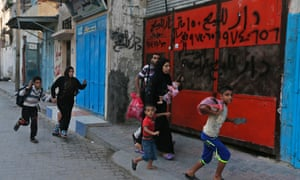 Palestinians run for shelter as they hear bombing in the distance while they flee their homes in the Shajaiyeh neighborhood of Gaza City