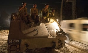 Israeli soldiers ride on an armoured personnel carrier  near Israel's border with the Gaza Strip.