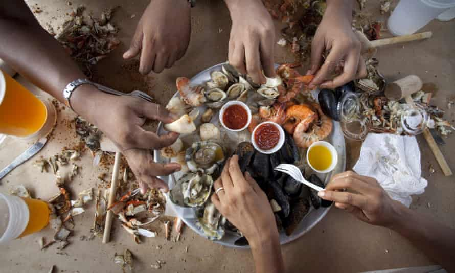 People sharing platter of shellfish