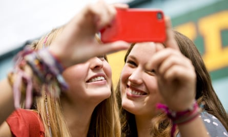 Two teenage girls taking a photograph of themselves.