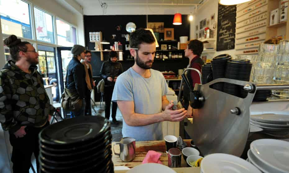 A man makes coffee at a boutique cafe in Brixton Village in south London.
