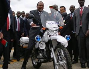 Kenyan president Uhuru Kenyatta test-rides a police motorbike made by Toyota in Nairobi, Kenya, 16 July 2014.