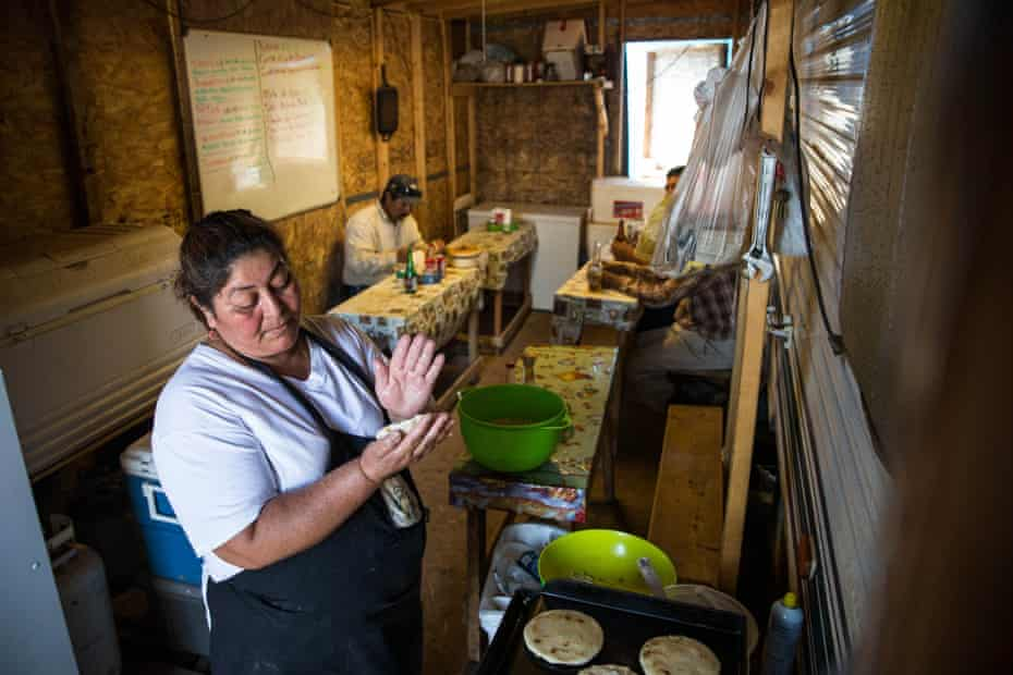 A woman makes tortillas in a make-shift restaurant, constructed of plywood and two-by-fours and attached to a motorhome in Watford City, near Williston.