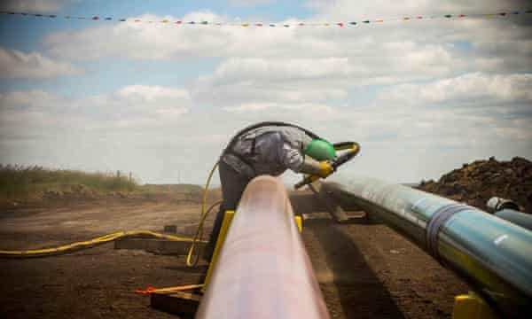 A worker sandblasts a section of pipeline.
