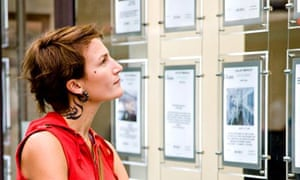 Woman looks at property ads in estate agents