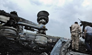 A Ukrainian serviceman stands next to the wrecked undercarriage of Malaysia Airline flight MH17