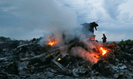 Flames and smoke rise from the debris at the crash site.