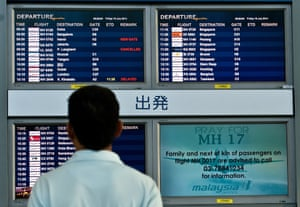 A Malaysian man looks at flight information screens displaying a solidarity message for Malaysia Airlines flight MH17 at Kuala Lumpur International Airport in Sepang on July 18, 2014.