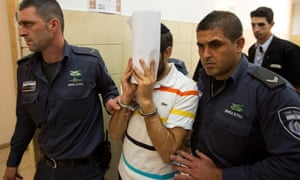 A 29-year old Israeli, center, is escorted by prison guard officers after being indicted with the death of Mohammed Abu Khdeir, 16, whose charred body was found after he was reported kidnapped, at the district court in Jerusalem, Thursday, July 17, 2014. (AP Photo/Sebastian Scheiner)