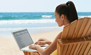 Mixed race woman using laptop on beach