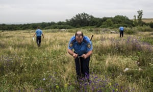 A police officer ties a white ribbon to a stake to mark where human remains have been found.