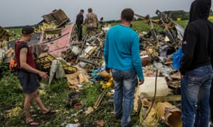 Men look at the wreckage of the plane.