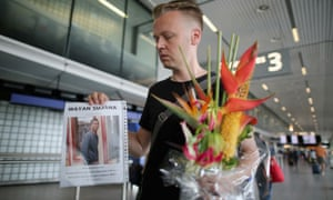 Arthur Laumann holds a floral tribute and photograph of family friend Wayan Sujana of Bali, believed to have been on Air Malaysia flight MH17.