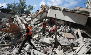 Members of Palestinian rescue services inspect the rubble of building, destroyed by an Israeli strike.