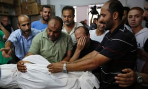 Relatives gather at a hospital morgue around the body of a member of the Abu Tawela family killed overnight by an Israeli strike.