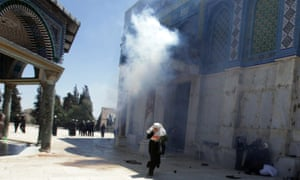 A palestinian girl runs away from exploding tear gas at the Dome of the Rock on the Temple Mount, or El Hareem el Sharif (The Noble Sanctuary) in Jerusalem after Friday prayers when Palestinians protested against Israeli attacks in Gaza.