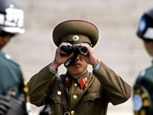 A North Korean soldier looks toward the South side through a pair of binoculars in between two South Korean soldiers at the demilitarized zone (DMZ) in the border village of Panmunjom between the two Koreas, in 2003.