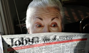 A surprised looking woman pensioner surveys her local paper