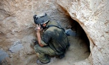 An Israeli soldier stands at the entrance of a tunnel beneath the border between Gaza and Israel