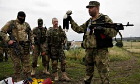 A pro-Russia fighter holds up a toy found among the debris at the crash site of MH17
