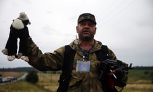 A pro-Russian separatist holds up a stuffed toy found at the crash site of Malaysia Airlines flight MH17, near the settlement of Grabovo in the Donetsk region, July 18, 2014