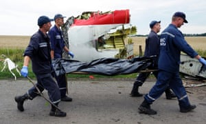 Rescue workers carry the body of a passenger killed when Malaysia Airlines flight MH17 was shot down over eastern Ukraine on Thursday