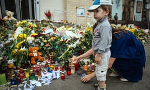 A young boy outside the Netherlands embassy in Kiev, where dozens of bouquets have been laid in commemoration of the 189 Dutch passengers who died when flight MH17 was shot down over eastern Ukraine on Thursday.