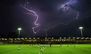 Players take cover after the postponement of the pre-season friendly football match between Dartford and Leyton Orient in Dartford, Kent.