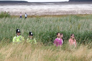 Police and spectators watch the drama from the tall grass beside the 13th green.