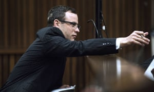 Oscar Pistorius receives a note from his defence team as he is seated in the dock during his murder trial at the high court.