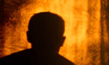silhouette of man/male on wall, cast by orange light /sunset.