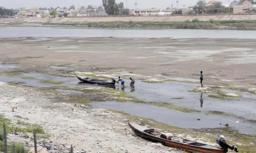 Iraqi men move a boat that was stuck on the banks of the Euphrates river in Twairij, roughly 20 kilometres east of Karbala, due to a decline in the water level after supplies were blocked by anti-government fighters who control access to a dam further upstream in conflict-hit Anbar province on April 8, 2014.