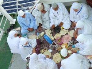 Passengers between Egypt and Jordan prepare their iftar as they wait for the sunset prayer to be called from the bridge of the ship. These passengers, dressed in new white robes, are making the umrah pilgrimage to Mecca.