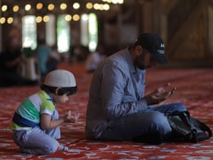 'A Turkish man and his son are praying at the Blue Mosque in Istanbul on the first day of the fasting month of Ramadan in Turkey.'