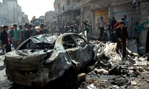 People gather at the site of two car bomb attacks in Homs, Syria