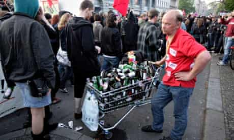 A man collects bottles as a May Day rally passes through Berlin's Kreuzberg district